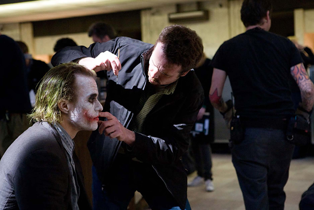 Prosthetics makeup supervisor Conor O'Sullivan adjusts Ledger's prosthetic scars on location in Chicago. © Warner Bros. Entertainment Inc
