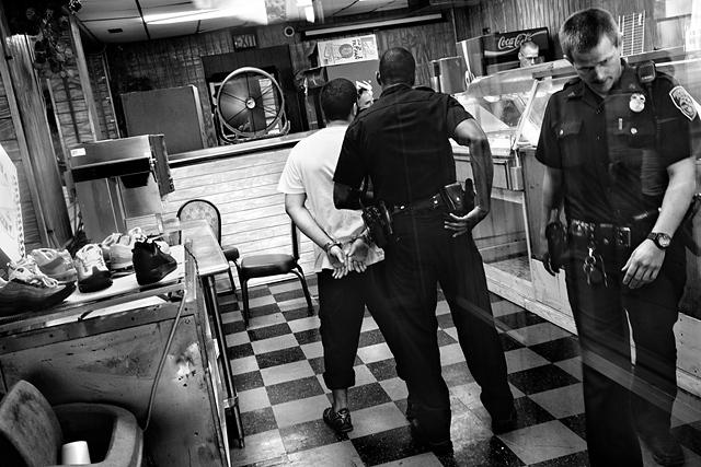 Un gérant de fast-food au nord-est de Rochester est interrogé, soupçonné d'avoir menacé un client avec un fusil de chasse. Rochester, état de New York. États-Unis, 2012 © Paolo Pellegrin / Magnums Photos / Postcards from America